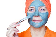 Cosmetic mask on the face. Close-up portrait of a beautiful young woman with a towel on her head having skin care treatments. She royalty free stock photography