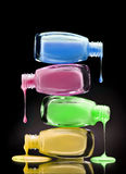 Cosmetic nail polish dripping from open bottles on black background. Close up Royalty Free Stock Image