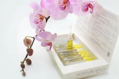 Cosmetic oil. Serum Ampules in the box with pink orchid around Royalty Free Stock Image