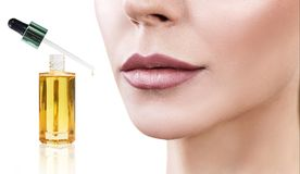 Cosmetic oil applying on face of young woman. Stock Photo