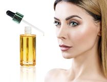 Cosmetic oil applying on face of young woman. Stock Image