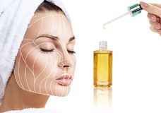Cosmetic oil applying on young woman with lifting lines. Beauty therapy concept. Graphic lines showing facial lifting effect on skin Royalty Free Stock Photo