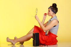 Cosmetic. Pin-up girl woman with bun applying makeup on yellow. Stock Photography