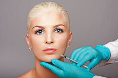 Cosmetic plastic surgeon injecting aesthetics face Royalty Free Stock Images