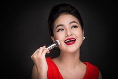 Cosmetic powder brush. Asian woman applying blusher on her cheek Stock Photography