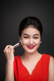 Cosmetic powder brush. Asian woman applying blusher on her cheek Royalty Free Stock Image
