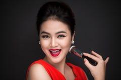 Cosmetic powder brush. Asian woman applying blusher on her cheek Royalty Free Stock Image