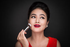 Cosmetic powder brush. Asian woman applying blusher on her cheek Royalty Free Stock Photography