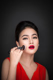 Cosmetic powder brush. Asian woman applying blusher on her cheek Royalty Free Stock Photo