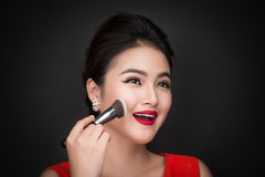 Cosmetic powder brush. Asian woman applying blusher on her cheek Stock Photo