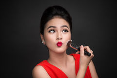 Cosmetic powder brush. Asian woman applying blusher on her cheek Royalty Free Stock Photos