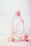 Cosmetic product bottle with micellar water or tonic for skin care, pink flowers, pastel color, front view. Beauty concept stock image