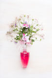 Cosmetic product glass bottle with pink liquid and bunch of flowers on white wooden background Royalty Free Stock Image