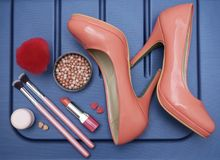 Cosmetic product, make up accessories and woman shoes in the blue background. Beauty treatment before vacation Royalty Free Stock Photography