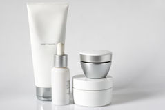 Cosmetic products. Set of cosmetic products in white and grey containers on light background Stock Photography