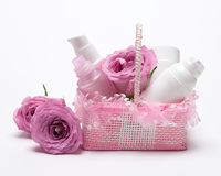 Cosmetic products as gift for girlfriend. Small pink wicker basket filled with various cosmetic products with rose flowers on light background. Romantic gift for Stock Photo