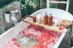 Cosmetic products on bath tub with flowers. Cosmetic products on bath tub with flower petals filling with water. Organic spa relaxation in luxury Bali outdoor royalty free stock photos