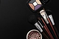 Eyeshadows, make-up brushes. Cosmetic products on black background and make up tools. Top view and mock up. Copy space. Cosmetic products on black background stock image