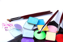 Cosmetic products - eyeshadows and makeup brushes Royalty Free Stock Photos