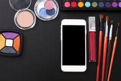 Cosmetic products and make up accessories on black background. Smartphone with blank screen. Top view and copy space. Summer color Royalty Free Stock Images
