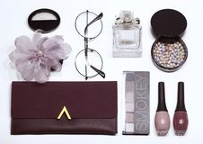 Cosmetic set: eyeshadow, nail polish, face powder, handbag on white background, flat stock photography