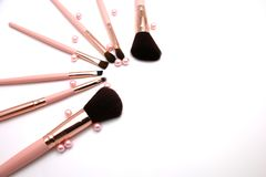 Cosmetic set of make up brush on pink color and pearl flatlay isolated on a white background royalty free stock image