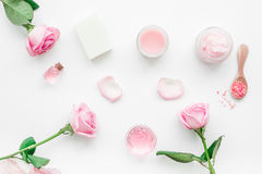 Cosmetic set with rose blossom and body cream on white desk background top view Royalty Free Stock Photos