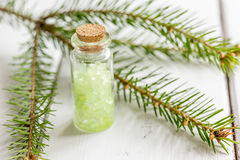 Cosmetic spruce salt in bottles with fur branches on white wooden table background Stock Photography