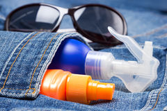 Cosmetic sunscreen products in jeans pocket Stock Images