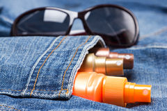 Cosmetic sunscreen products in jeans pocket. On the background of sunglasses. Skin care cosmetics containing sun protection factor Royalty Free Stock Images