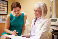 Cosmetic Surgeon Discussing Proceedure With Client In Office. Looking At Notes Smiling stock image