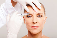 Cosmetic face lifting. Cosmetic surgeon giving face lifting injection to mature woman Royalty Free Stock Photos