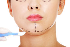 Cosmetic surgery concept. Female face in background of scalpel Stock Image