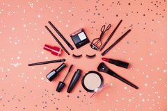 Cosmetic for woman makeup and beauty products decorated star confetti on coral table top view. Flat lay style