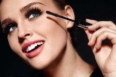 Cosmetici Bella donna con trucco perfetto che applica mascara fotografia stock