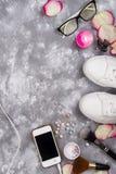 Cosmetici con profumo, il telefono e le scarpe da tennis su un fondo grigio con lo spazio della copia Fotografia Stock