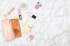 Cosmetici decorativi femminili e borsa cosmetica su un backgro di marmo Immagine Stock