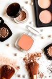Cosmetici decorativi schiacciati nudi sulla vista superiore del fondo bianco Fotografie Stock