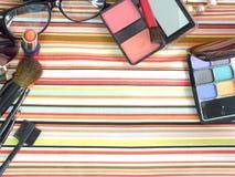 Cosmetici decorativi sul fondo della banda bianca e blu del tessuto Fotografie Stock