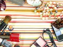 Cosmetici decorativi sul fondo della banda bianca e blu del tessuto Fotografia Stock