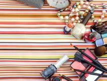 Cosmetici decorativi sul fondo della banda bianca e blu del tessuto Immagini Stock Libere da Diritti