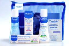 Cosmetici del bambino isolati su bianco Un insieme dei cosmetici naturali infantili da portare avanti sulla strada - Mustela Immagine Stock Libera da Diritti