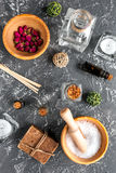 Cosmetici della stazione termale con sapone, sale, olio sulla vista superiore del fondo scuro Fotografia Stock