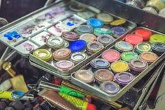 Cosmetici e spazzole di trucco nello spogliatoio vicino allo specchio Immagine Stock