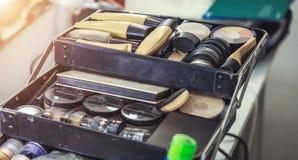 Cosmetici e spazzole di trucco nello spogliatoio vicino allo specchio Immagini Stock