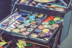 Cosmetici e spazzole di trucco nello spogliatoio vicino allo specchio Fotografia Stock