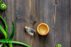 Cosmetici organici di vera dell'aloe L'aloe vera copre di foglie e lozione della stazione termale sul copyspace di legno di vista Immagine Stock