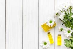 Cosmetici per cura di pelle con la camomilla Lubrifichi, insaponi sullo spazio di legno bianco della copia di vista superiore del fotografia stock