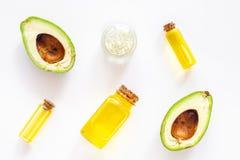 Cosmetici per cura di pelle Olio di avocado vicino alla metà dell'avocado sulla vista superiore del fondo bianco fotografia stock libera da diritti