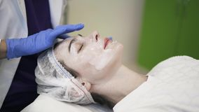 Cosmetician που εφαρμόζει την κρέμα στο πρόσωπο γυναικών s απόθεμα βίντεο